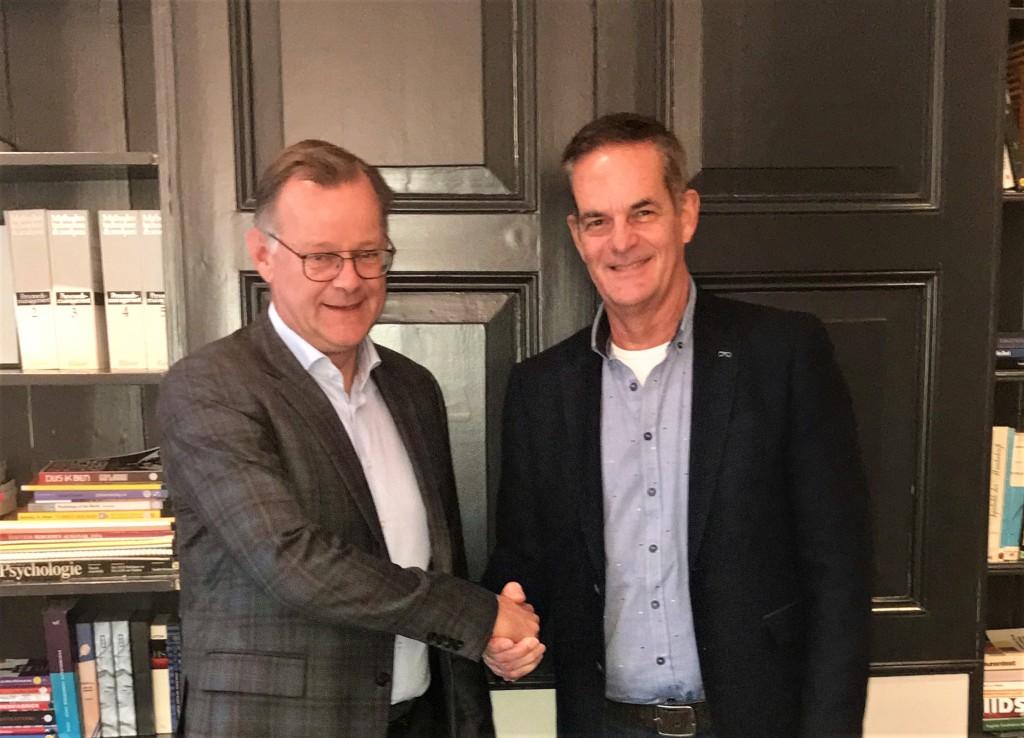 Marco ten Berge (links), directeur van St. Communicatie en Miel in 't Zand, directeur van st. Topsport for Life, schudden elkaar de hand op de nieuwe samenwerking.